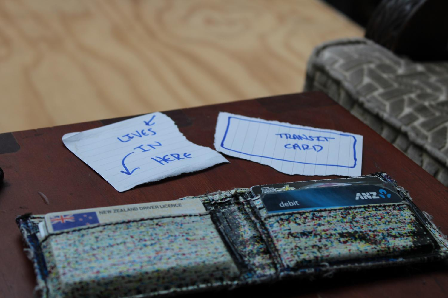 A close up photo of a table with my wallet folded open on it. A piece of paper represents my transit card as I no longer had it at the time of writing this post.