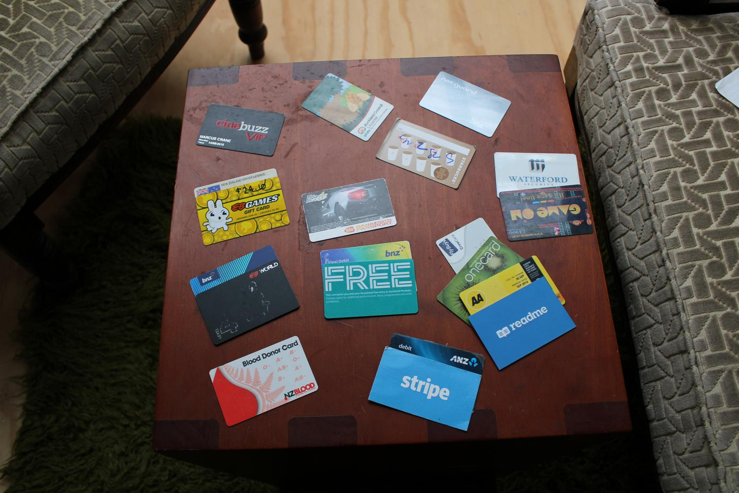 An aerial photo of a table with numerous cards scattered around. There are different types from loyalty cards to business cards, as described below.