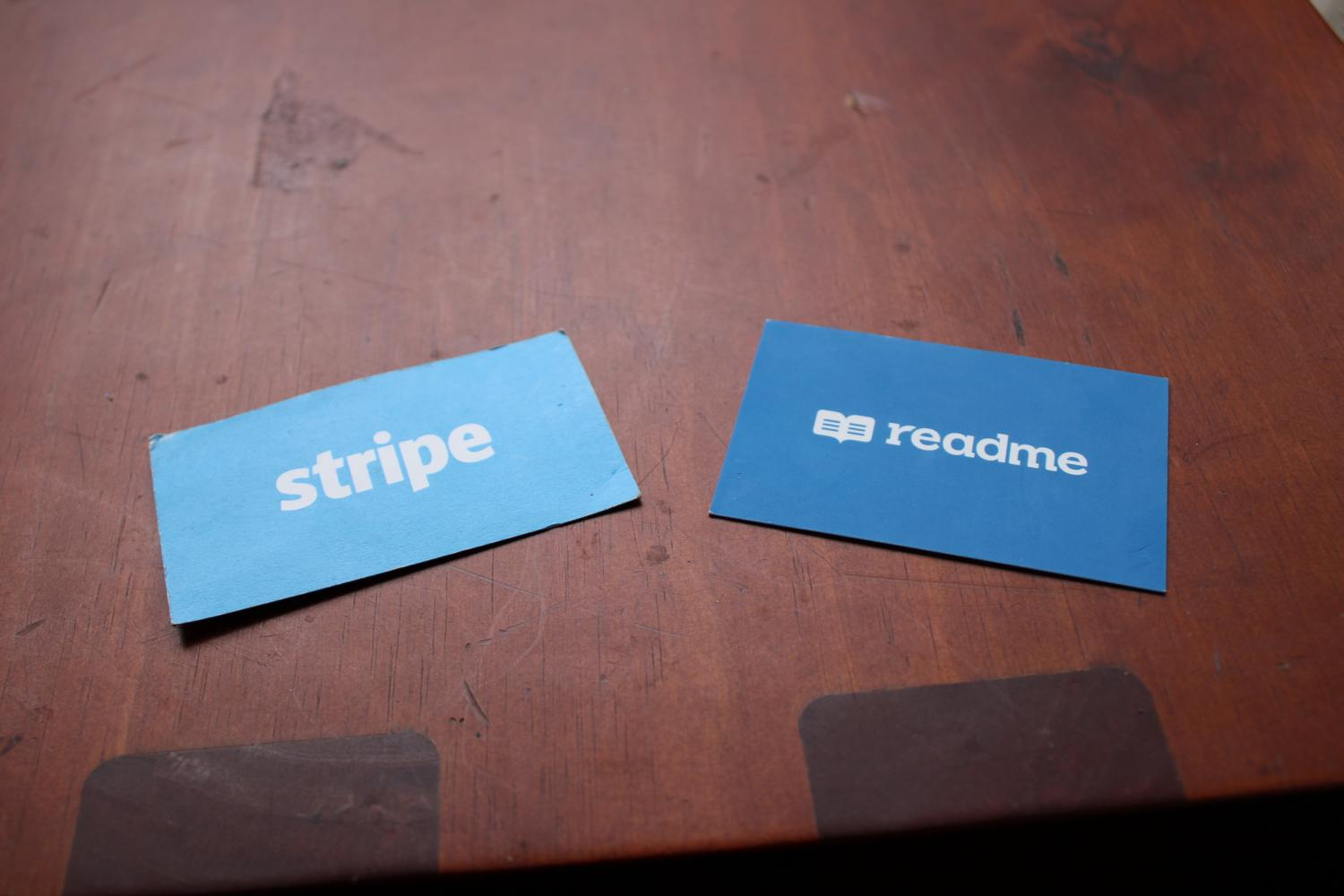 A close up photo of two business cards. One is for stripe.com and another is for readme.com.