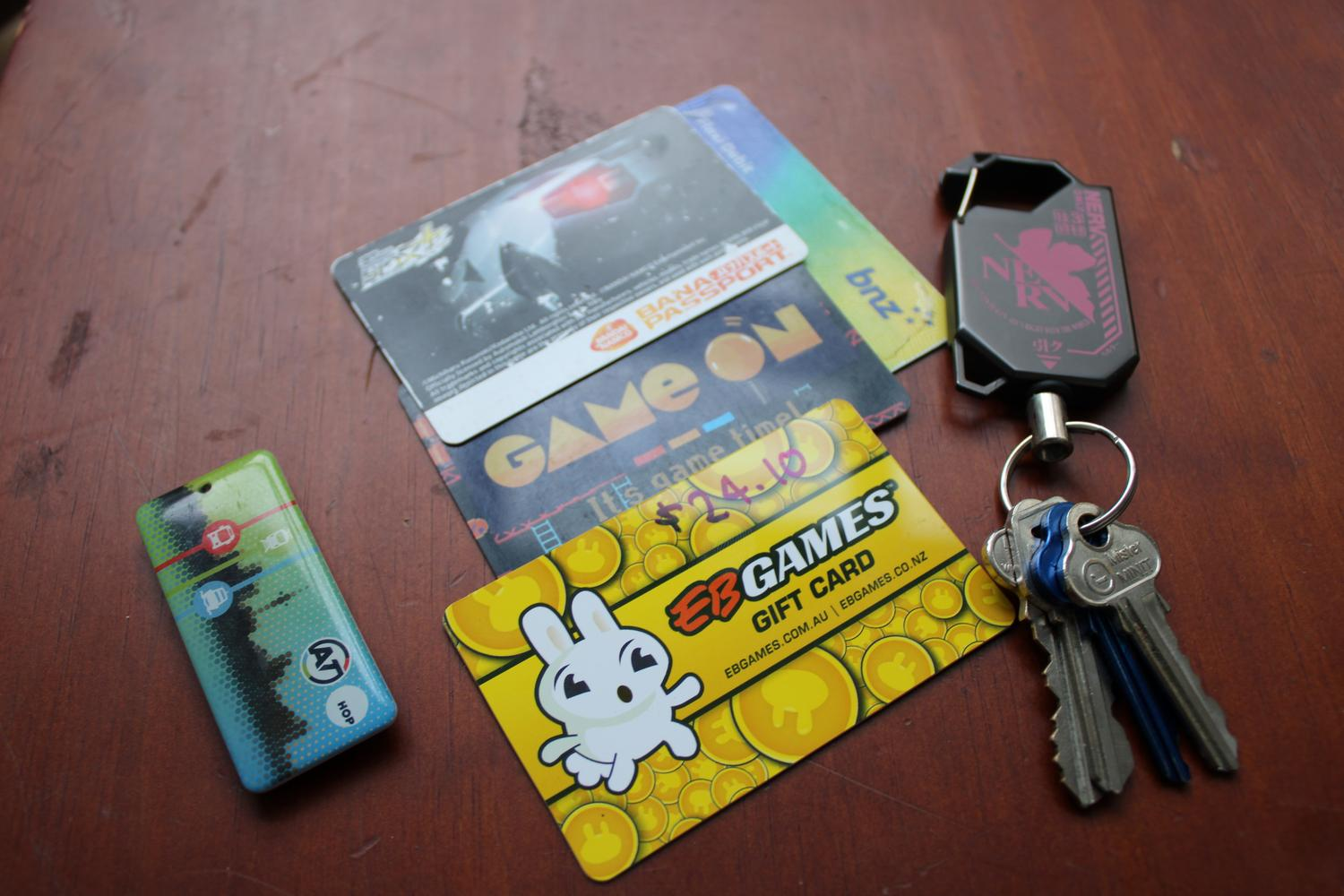 A close up photo of a table surface showing the smaller transit card to the left, a few remaining physical cards that I like to keep around and a carabiner containing various house keys.