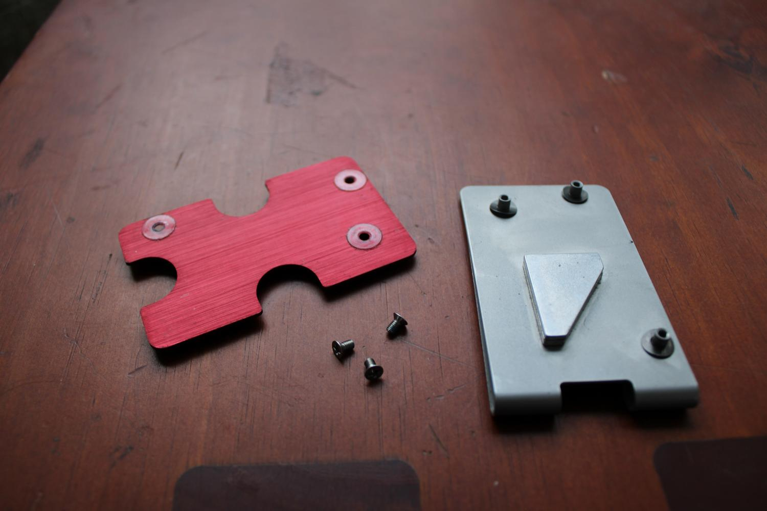 A close up photo of a table surface containing a metal device that has been unscrewed. The base plate is on the right with three little stands to provide room in between itself and the top plate. The idea is that the cards sit in between the gap. The top plate is red and sitting to the left of the base plate with three small screws sitting just below it.