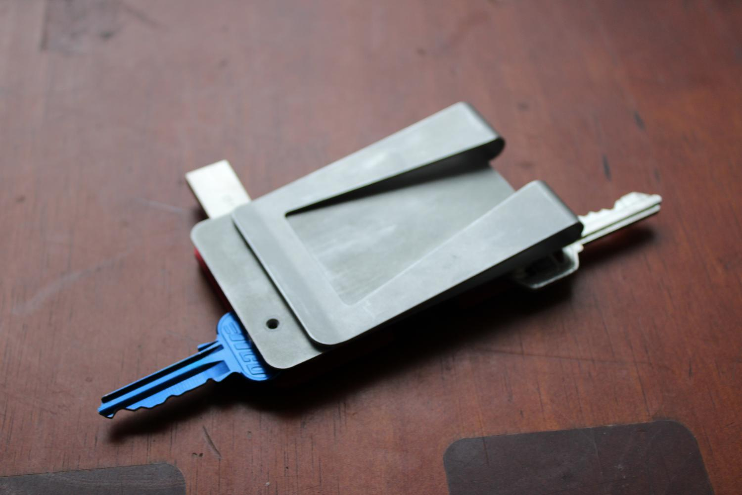 A close up photo of a table surface with the assembled metal wallet sitting on it. The wallet is upside down, with the keys and USB drive extended beyond the base plate. The bottom of the base plate is visible, as the wallet is upside down, and has a large clip at the bottom for slotting cards into.