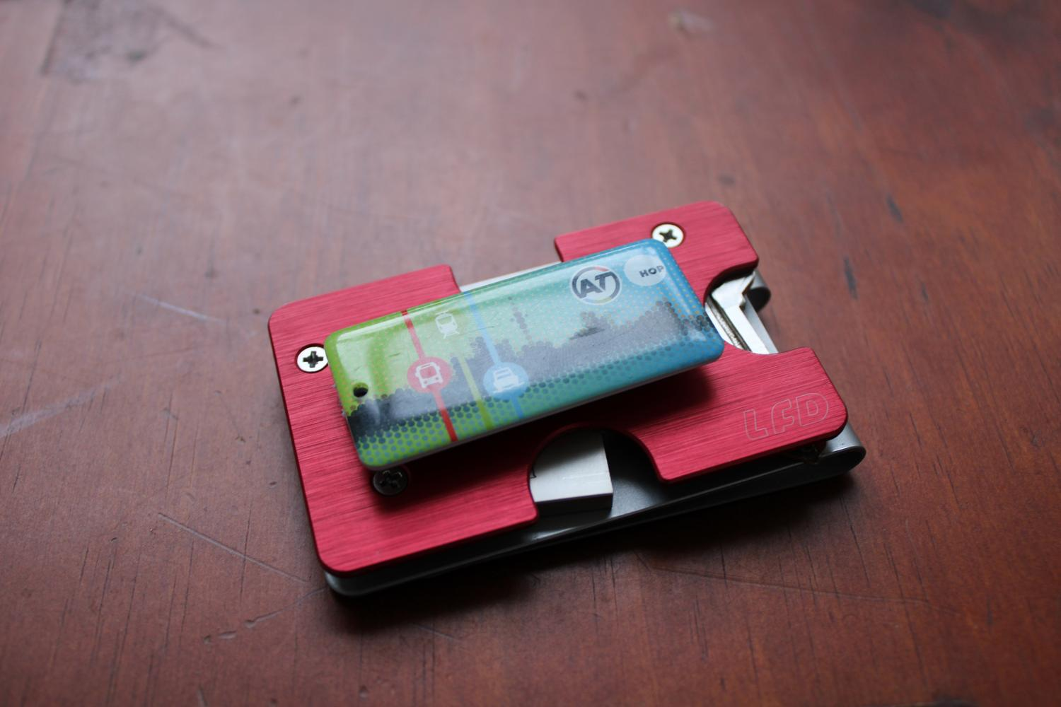 An aerial photo of the assembled metal wallet sitting on a table surface. It is positioned right side up this time showing the red top plate. On top of the red plate is the small badge sized transit card, seemingly hovering in place. It's actually attached to a velcro strip although you can't visually tell that from the photo.