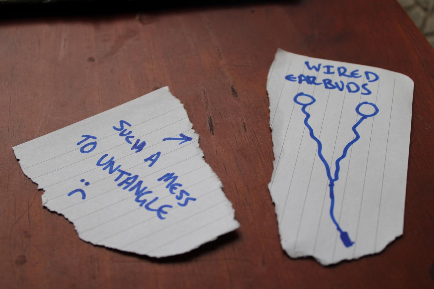 """A close up photo of a table surface with two pieces of paper. One on the left says """"Such a mess to untangle"""" with a sad face and an arrow pointing to the right. The piece of paper on the right is a ridiculously bad drawing of wired earbuds with text at the top that reads """"Wired earbuds"""". I no longer had the them in my position so this is supposed to be a placeholder for the real thing."""